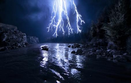 https://maessage.wordpress.com — foudre tombant sur une rivière où dérive une barque. C'est la nuit ; la rivière est bordée de rochers et d'une forêt très sombres • photo avec effets spéciaux (gravure rétroéclairée sur plexiglas peint en noir), 2013, de Matthew ALBANESE, photographe américain : « Box of Lightning » / « Boîte de Foudre »
