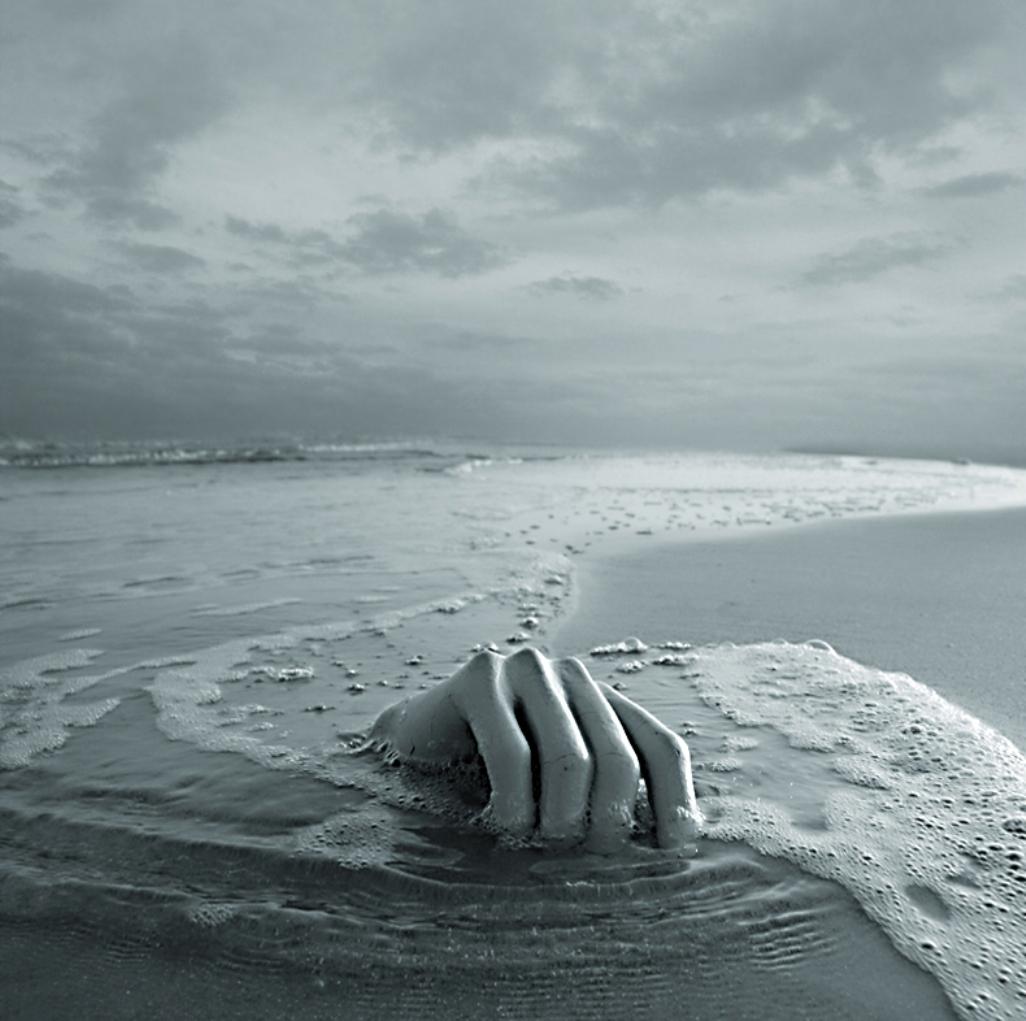 https://maessage.wordpress.com — main énorme et osseuse émergeant du sable au bord de la mer, parmi la mousse des vagues qui ont déferlé • photo noir & blanc